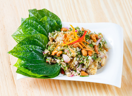 silver perch: Close up Deep fried barramundi with Thai style spicy salad wild betel leaf Stock Photo