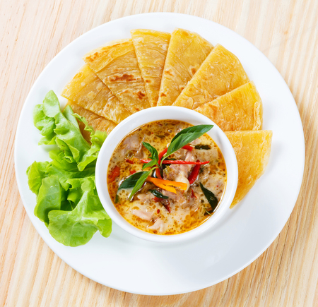 Close up Indian pancake served with chicken curry and green oak lettuce photo