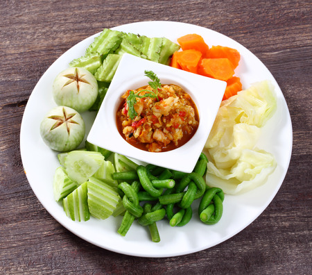 Close up spicy shrimp dip sauce served with raw and boiled vegetable photo
