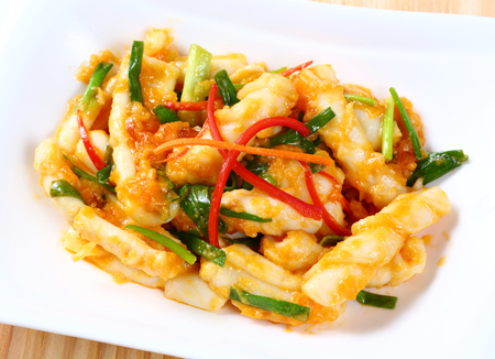 to stir up: Close up stir fried squid with salted egg yolk on white dish