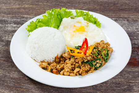 stir up: Close up Rice topped with stir fried minced pork and basil on white dish Stock Photo