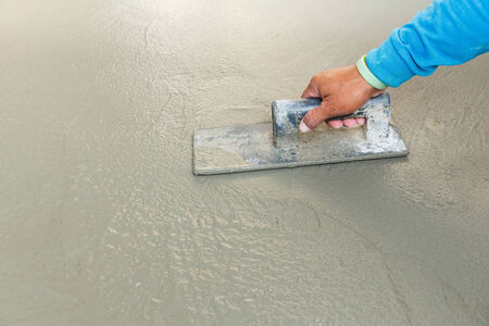 Close up worker hand using float to level surface of concrete Standard-Bild