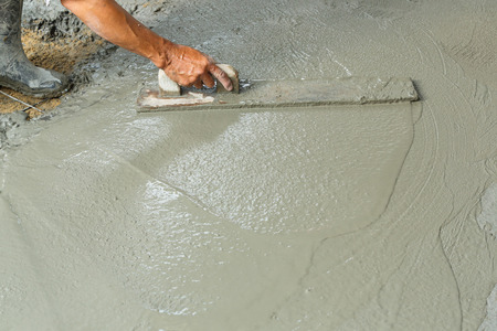 leveling: Close up worker hand using float to level surface of concrete Stock Photo