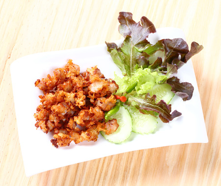 knees up: Close up Deep fried sour fermented chicken knees tendon served with bird chili sliced cucumber and lettuce
