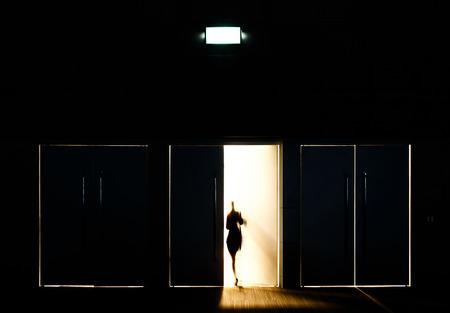 inauguracion: Puerta abierta con el desenfoque de movimiento de un hombre y de la luz que entra por el espacio Foto de archivo