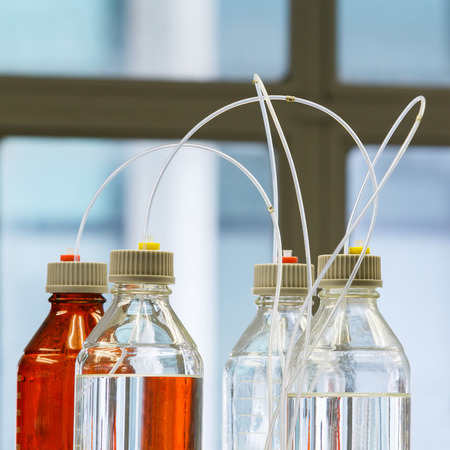 analytical chemistry: Close up clear and amber color bottle with plastic hose for High performance liquid chromatography - HPLC Stock Photo