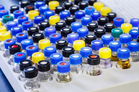 Vials with inserts and crimp septum caps in plastic rack for liquid analysis photo