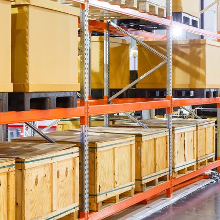 창고의 스틸 선반 시스템에 종이와 목재화물 상자를 닫습니다.