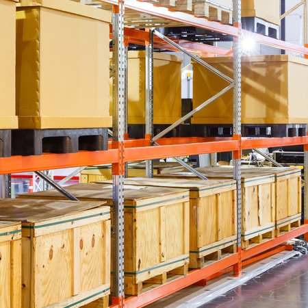 Close up paper and wooden cargo box on steel shelf system in warehouse Archivio Fotografico
