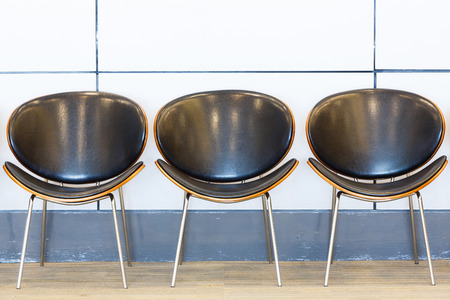 Close up row of waiting chairs and white color wall in office building photo