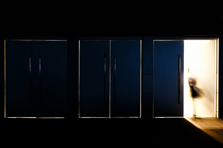 dark room: Door opened with motion blur of a man and light coming through the space