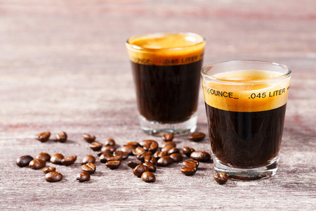 Close up espresso shot glass and coffee bean on old wooden table photo