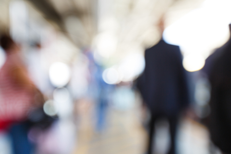 Abstract blurred people walking or standing in train station photo