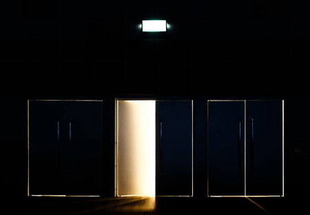 One door opened and light coming through the space mean hope or Exit of life photo