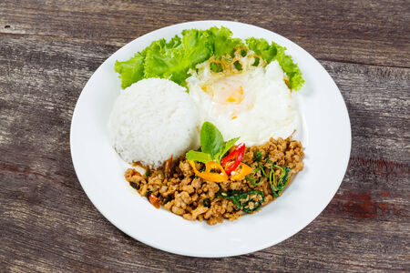 Close up Rice topped with stir fried minced pork and basil photo