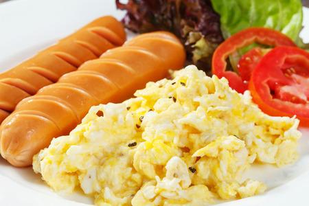 papas doradas: Cierre de salchichas y huevos revueltos servido con rodajas de tomate y lechuga Foto de archivo