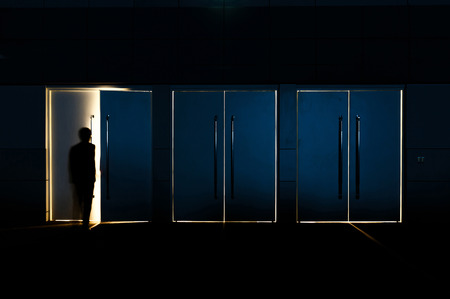 Door opened with motion blur of a man and light coming through the space photo