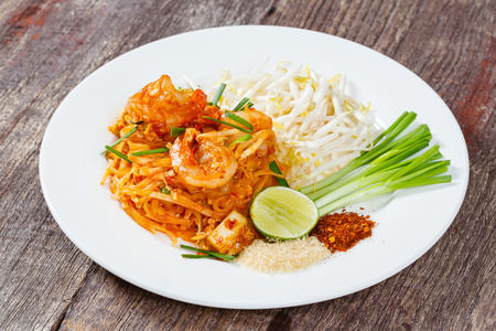 Close up Pad Thai with prawn or shrimp served with sliced lime sugar ground chili and Chinese Chives photo