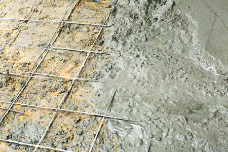 Close up wire mesh and wet cement in concrete floor pouring process