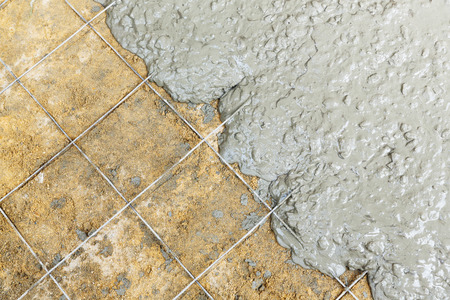 Close up wire mesh and wet cement in concrete floor pouring process photo