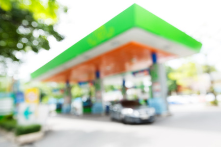 fill in: Blurry gas station with car fill up fuel in daytime