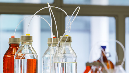 Close up clear and amber color bottle with plastic hose for High performance liquid chromatography - HPLC photo