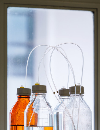 high performance: Close up clear and amber color bottle with plastic hose for High performance liquid chromatography - HPLC Stock Photo