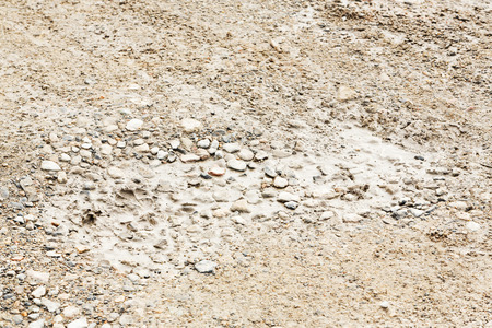 Close up bumpy stone road with water in potholes photo