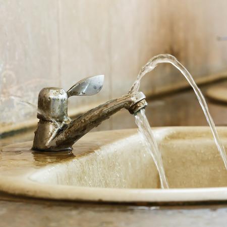 더러운 오래 된 화장실에서 누수와 망치 밸브를 닫습니다