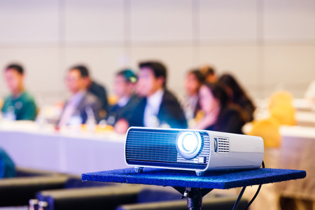 Close up projector in conference room with blurry people background 스톡 콘텐츠