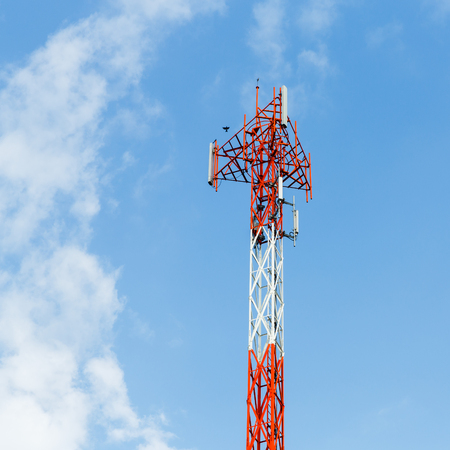 Close up red and white color antenna repeater tower on blue sky photo