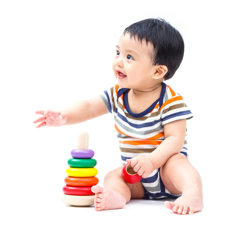 Cute asian baby playing toy isolated on white