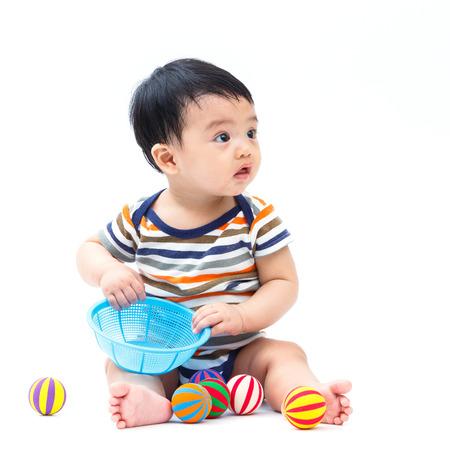non toxic: Beb� asi�tico lindo que juega el juguete aislado en blanco