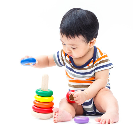 Cute asian baby playing toy isolated on white photo