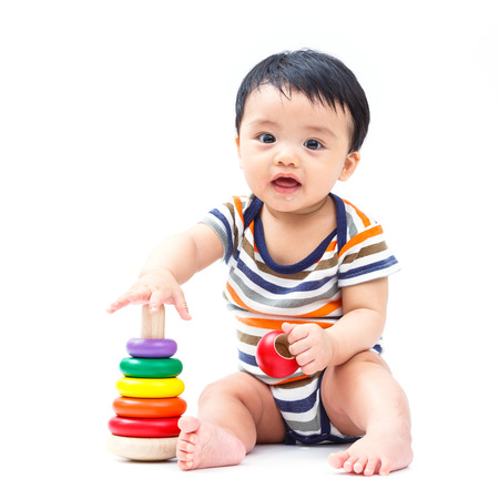 children clothing: Cute asian baby playing toy isolated on white