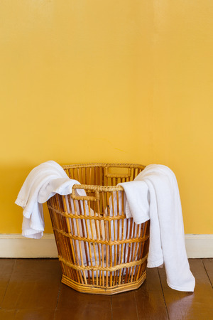 Close up white color used towels in wicker basket in laundry room photo