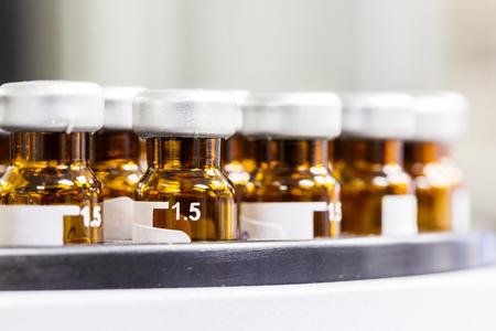 crimp: Close up amber color vials with inserts and crimp septum caps Stock Photo