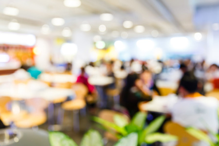 Abstract blurred people eating in food center photo