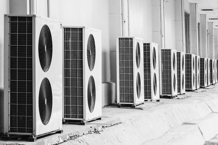 and the air: Group of air conditioner outdoor units outside of building Stock Photo