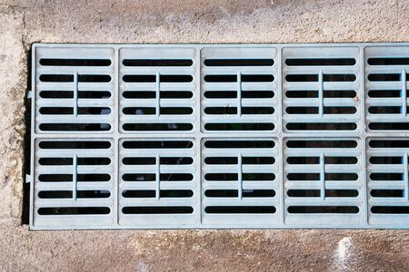 grates: Close up old and weathered plastic trench drain grates in city