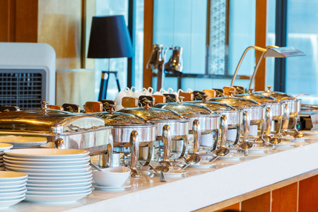 Close up stainless steel countertop food warmer and dish on table, catering concept Standard-Bild