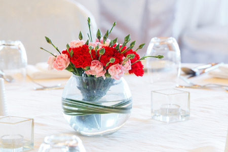dinning table: Close up red and orange color carnation flower bouquet in old glass vase on dinning table