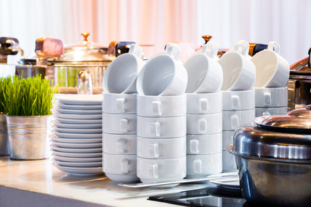 Close up stacks of white color ceramic coffee cup and dish ready for use in party room, catering service
