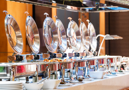 buffet: Close up stainless steel countertop food warmer and dish on table, catering concept Stock Photo