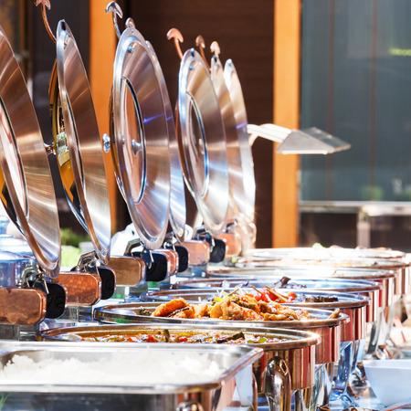 ステンレス カウンターは、暖かい食べ物を閉じるし、コンセプトをケータリング テーブルの上に皿 写真素材