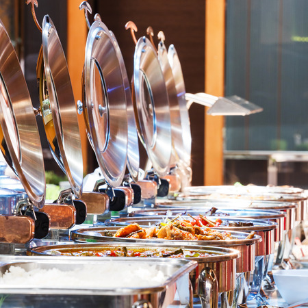 buffet dinner: Close up stainless steel countertop food warmer and dish on table, catering concept Stock Photo