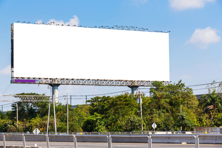Blank billboard on blue sky ready for new advertisement beside highway photo