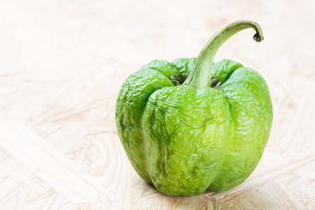 puckered: Close up wrinkled green bell pepper on particle board