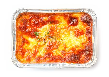 deep focus: Close up beef lasagna in foil tray isolated on white, deep focus image, delicatessen