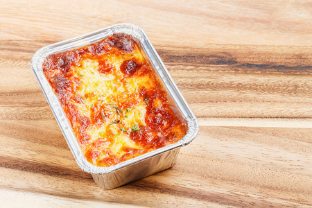 deep focus: Close up beef lasagna in foil tray on wooden chopping board, deep focus image, delicatessen